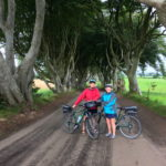 Couple with bikes at the Dark Hedges Causeway Coast self-guided bike tour with Ireland by Bike