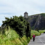 Solo cyclist going towards Mussenden Temple Causeway Coast bike tour with Ireland by Bike cycling tours