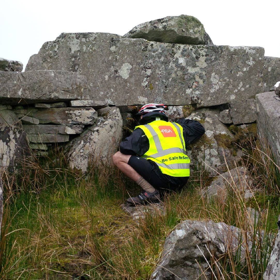 Cyclist looking into court tomb Co Donegal