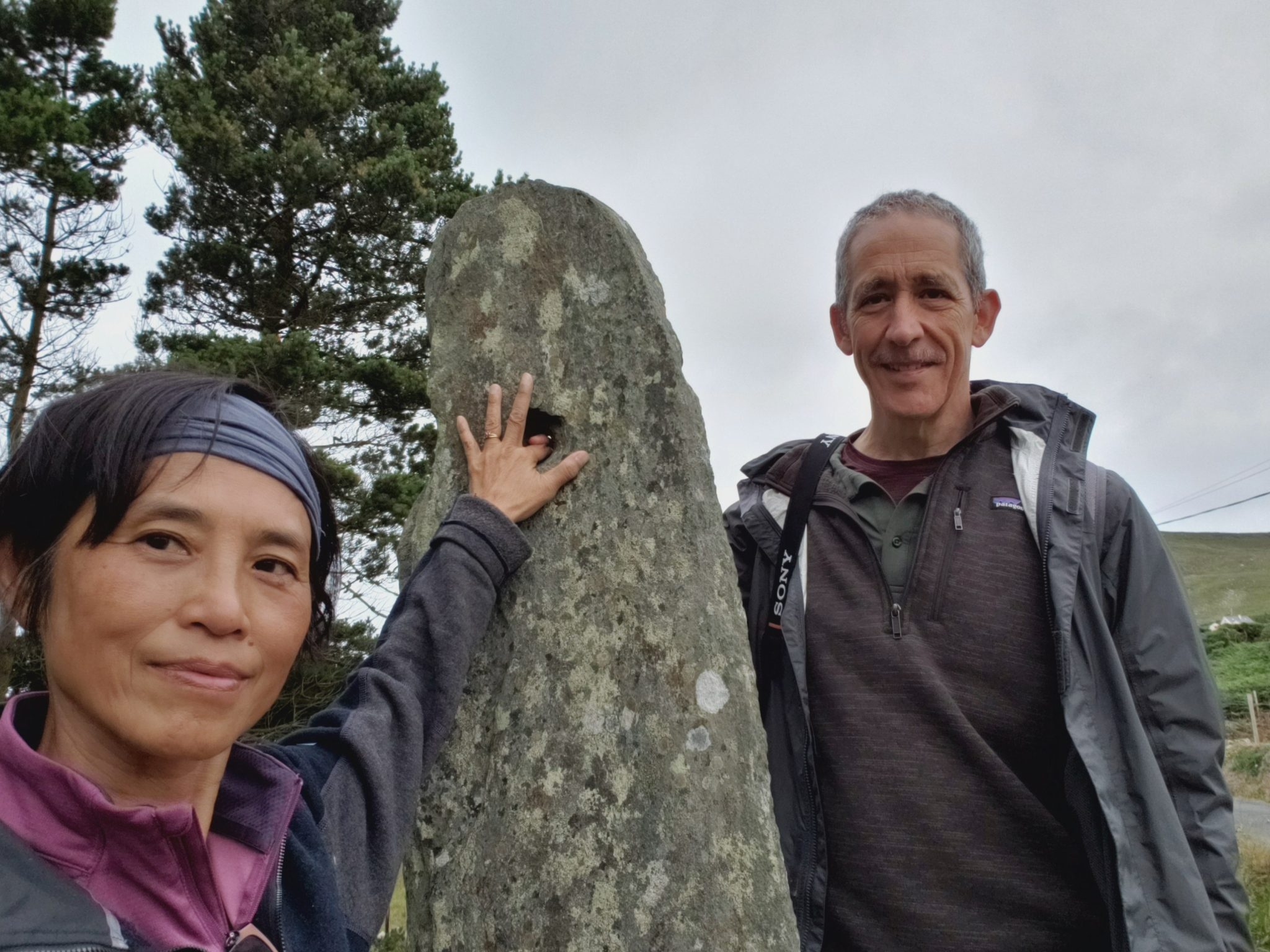 Two cyclists at one of the Megalithic standing stones on Turas Cholmcille